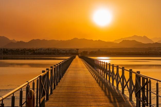 Ярко-оранжевый закат над силуэтом пустынных гор египта и береговой линией с морской водой