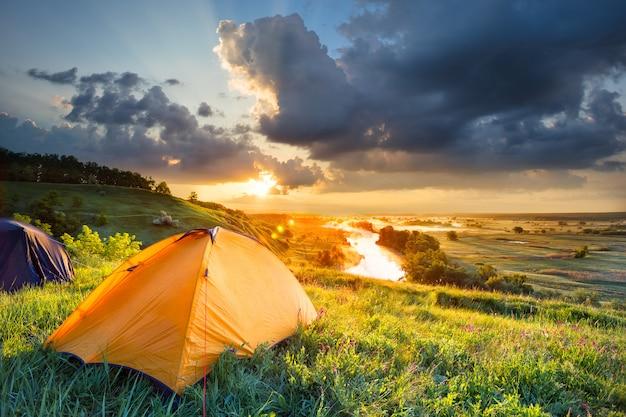 Ярко-оранжевая палатка на склоне холма под рекой