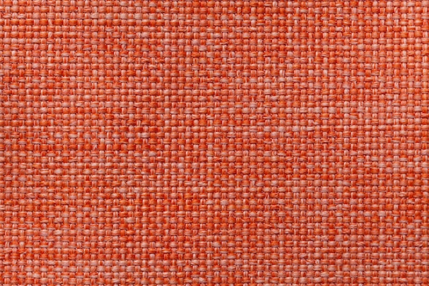Bright orange textile background with checkered pattern, closeup. structure of the fabric macro.