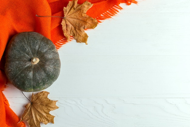 Bright orange warm shawl, pumpkins and dry yellow leaves on a white background, autumn mood, copyspace.