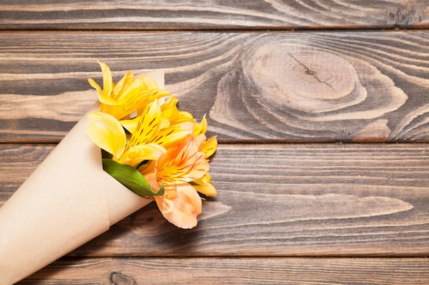 Bright orchid flowers are packaged in kraft paper.