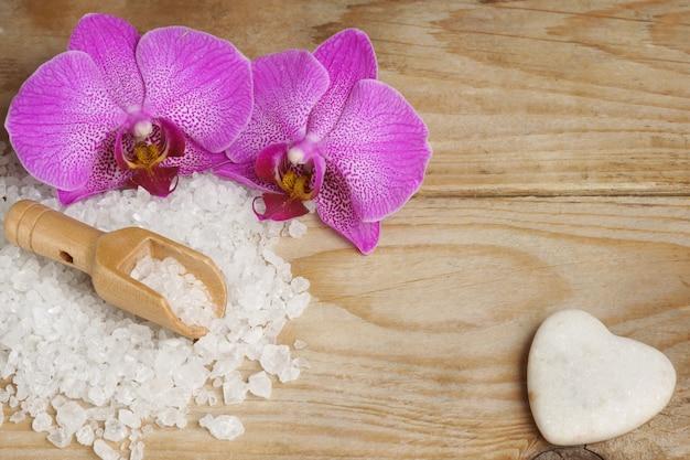 白いバスソルトと木製のテーブルの上のハート型の石の横にある明るい蘭の花