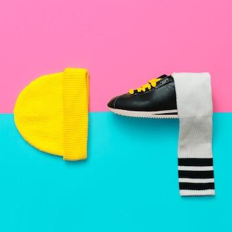 明るい服。最小限のファッションクリエイティブアート。スタイリッシュなスニーカーと靴下。ビーニー