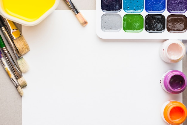 Bright paints and brushes near paper