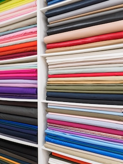Яркая палитра красочного крупного плана трикотажных полотен. образцы ярких тканей на полках в магазине.