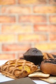 Фото яркой выпечки с кексом в городском кафе, кирпичная стена