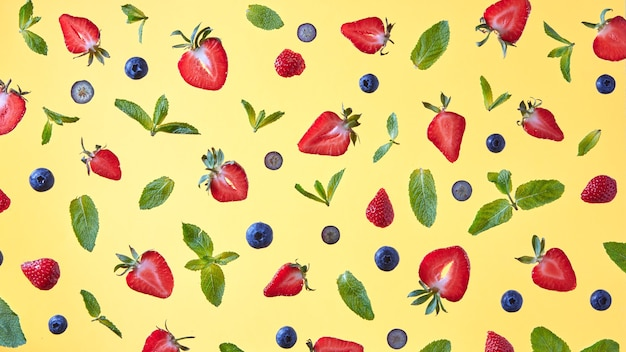 Bright pattern of halves of strawberries, blueberries and mint leaves