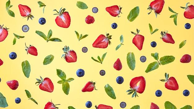 イチゴ、ブルーベリー、ミントの葉の半分の明るいパターン