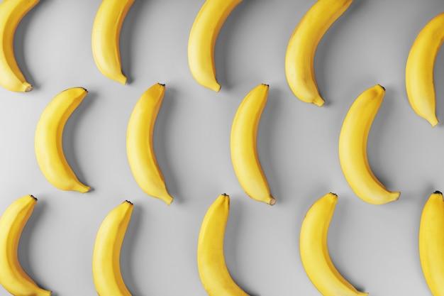 Яркий узор из желтых бананов на сером фоне. вид сверху. плоская планировка. фруктовые узоры