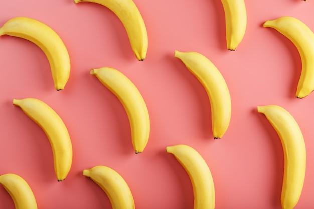 ピンクの背景に黄色のバナナの明るいパターン。上からの眺め。フラットレイ。フルーツパターン