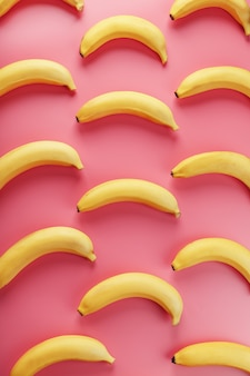 Яркий узор из желтых бананов на розовом фоне.