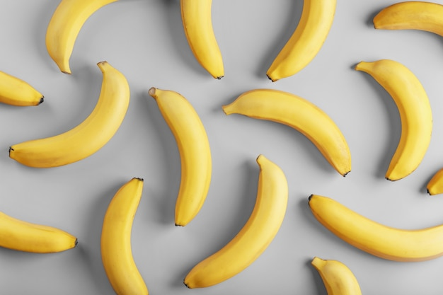 Bright pattern of yellow bananas on a gray surface