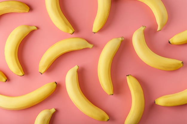 Bright pattern of yellow bananas on a pink background. view from above. flat lay. fruit patterns