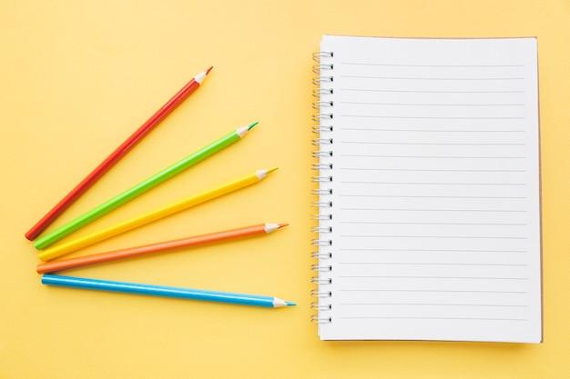 Яркие карандаши возле блокнота