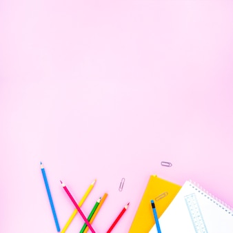 Bright pencils and notebooks laid in random way
