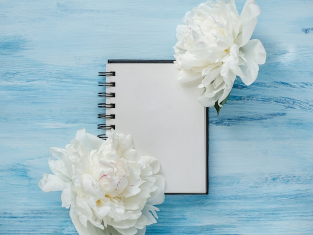 Яркие пионы, пустая страница блокнота на деревянном столе
