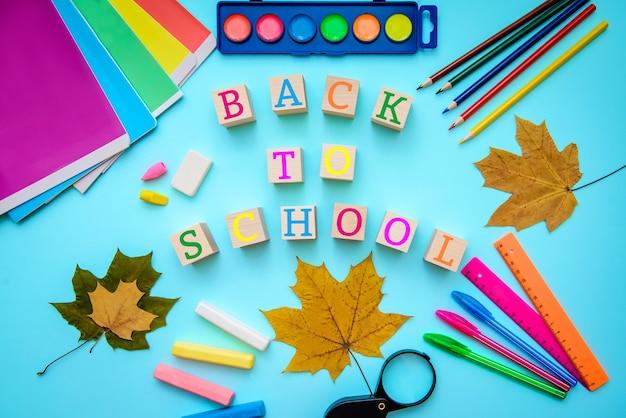 Яркая карточка-картинка с надписью: снова в школу с тетрадями, красками, цветными карандашами, ручками, линейками, мелом, кубиками, желтыми осенними листьями на синей поверхности