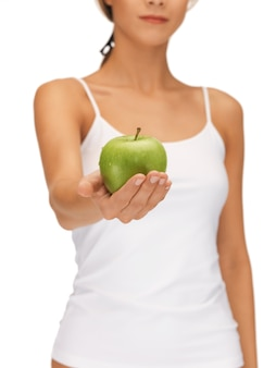Bright picture of female hands with green apple