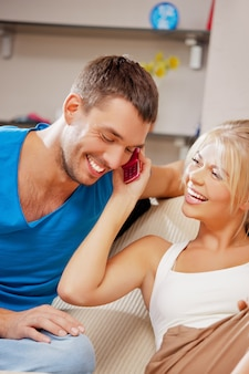 Bright picture of happy couple with cellphone (focus on woman)