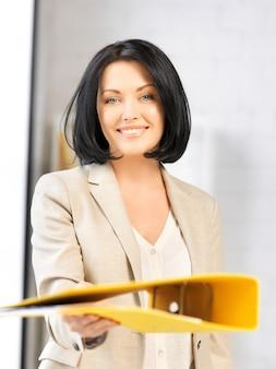 フォルダーを持つ美しい女性の明るい写真