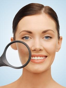 にきびの上に虫眼鏡で美しい女性の明るい写真