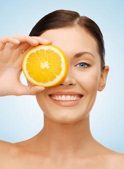 오렌지 슬라이스를 가진 아름다운 여성의 밝은 사진