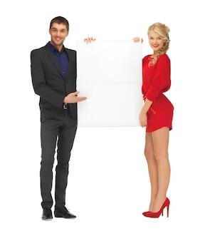 大きな空白のボードを保持しているカップルの明るい写真