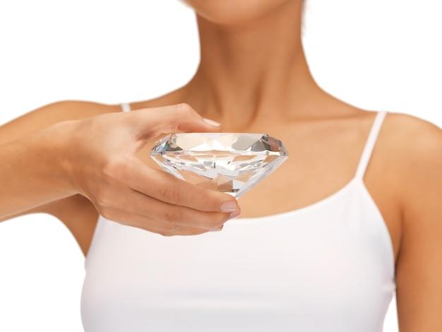 Яркая картина женских рук с большим бриллиантом