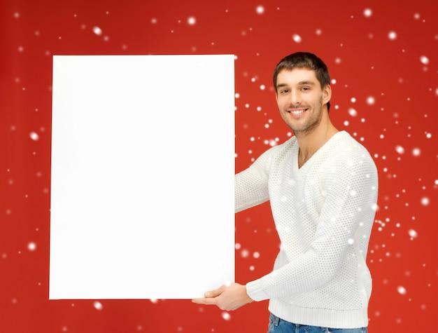 大きな空白のボードを持つハンサムな男の明るい写真。
