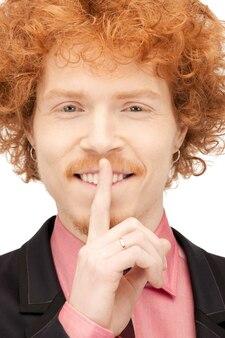 입술에 손가락을 대고 잘생긴 남자의 밝은 그림