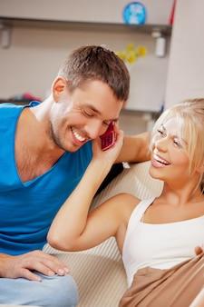 Яркое изображение счастливой пары с мобильным телефоном (фокус на женщину)