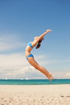 해변에서 행복 점프 여자의 밝은 그림.