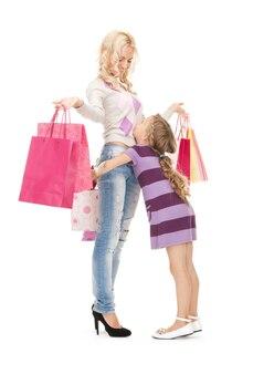 幸せな母と買い物袋を持つ少女の明るい写真