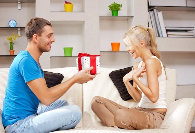 贈り物と幸せなロマンチックなカップルの明るい写真