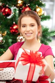 ギフトボックスとクリスマスツリーと幸せな女性の明るい写真......