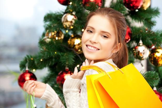 ショッピングバッグとクリスマスツリーと幸せな女性の明るい写真.....