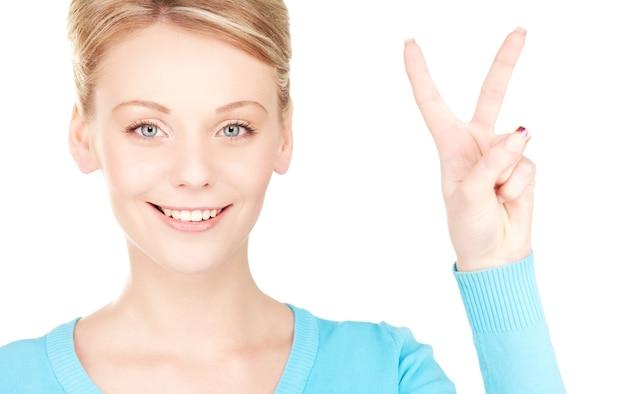 승리 기호를 보여주는 사랑스러운 금발의 밝은 그림
