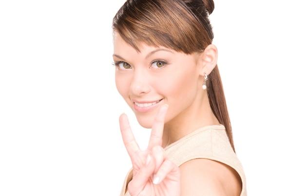 승리 기호를 보여주는 사랑스러운 여자의 밝은 그림