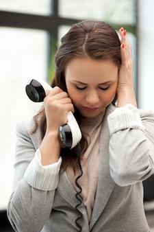 Яркая фотография грустной бизнес-леди с телефоном
