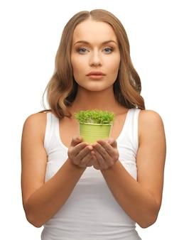 Яркая картина женщины с зеленой травой в горшке