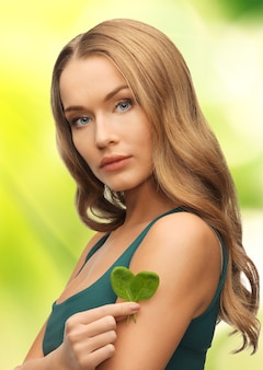 손바닥에 시금치 잎을 가진 여자의 밝은 그림