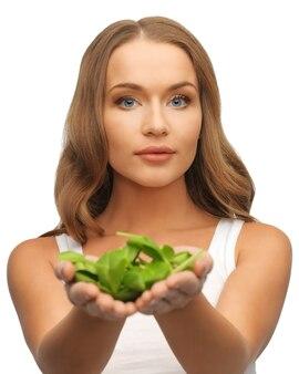 Яркая картина женщины с листьями шпината на ладонях