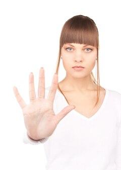 停止ジェスチャーをしている若い女性の明るい写真