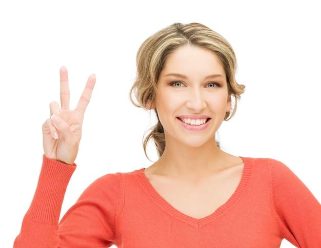 勝利の兆候を示す若い女性の明るい写真