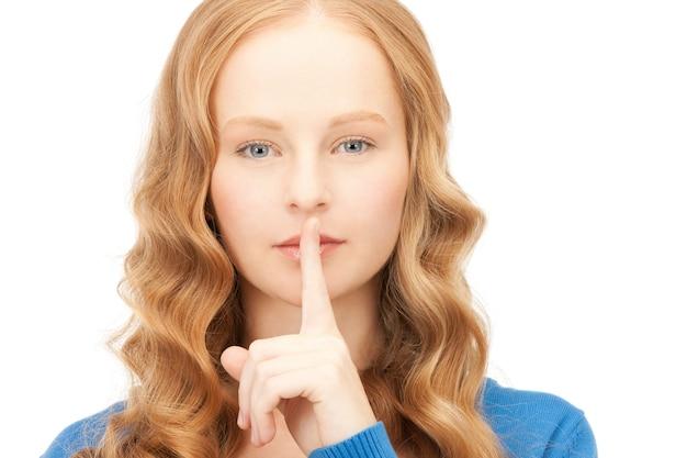 입술에 손가락을 대고 있는 젊은 여성의 밝은 사진