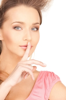 唇に指を持つ若い女性の明るい写真