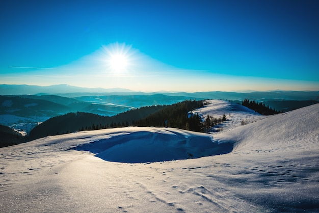Bright picturesque sunny panorama of the ski slopes of the valley and the hills and dense forest on a frosty winter day. ski resort concept.