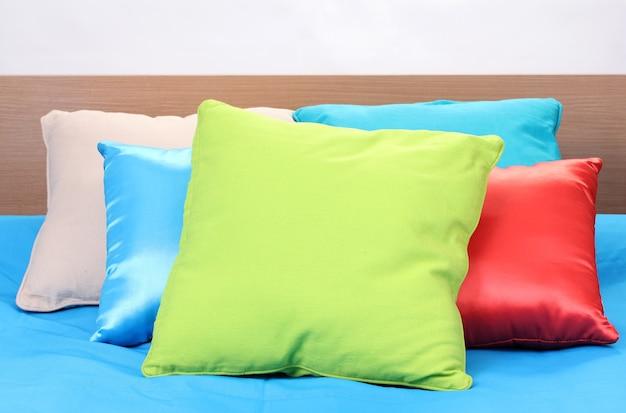 白いスペースのベッドの上の明るい枕