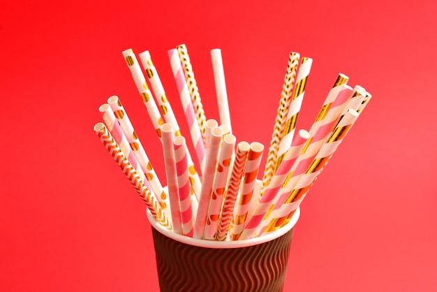 Ярко-розовые и золотистые трубочки в бумажном стаканчике. скопируйте пространство.