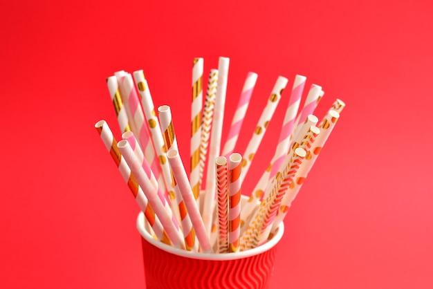 紙コップの明るいピンクと金色の細管。スペースをコピーします。